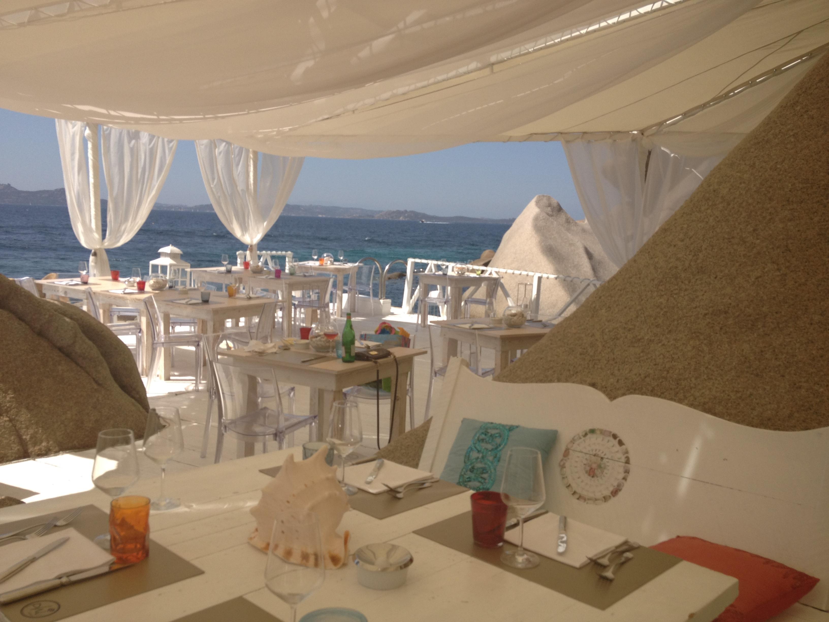 No verão europeu de 2012 passei uma semana na Sardegna, lugar lindissimo, com a água do mar em um verde indescritível. Adorei todas as praias, mas a que mais me chamou atenção foi esta pequena enseada particular, chamada Phi Beach. O lugar é de dificil acesso (minha dica estando na Sardegna é alugar um carro), perto de Porto Cervo, no norte da ilha, porém o charme e beleza do complexo vale a procura. Phi Beach é um beach club muito bem decorado e que conta com um restaurante excepcional. O design caiu como uma luva para o lugar, que tem serviço 5 estrelas para o day use. Sugiro chegar cedo para curtir a praia em bangalows unicos, depois almoçar no restaurante e aproveitar o por do sol (tramonto) ao som do DJ residente Mirko de Crescenzo. Seu dono é adorador de carros esportivos (ao chegar em Phi, voce pode ver uma Ferrari Vermelha estacionada a sua esquerda, majestosa no alto de uma colina, e um hostess super simpatico. Durante o verão ele pode ser encontrado almoçando com grupos de amigos ou em eventos que a Audi e a Veuve Clicquot fazem em Phi. Antes de ir embora, da uma olhadinha para trás e procure ver o reflexo da lua no mar... E imperdivel!