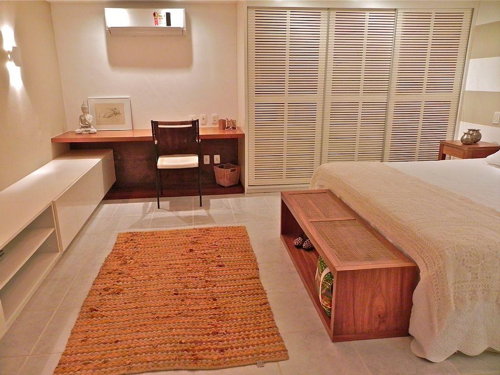 Visao ampla do quarto, com bancada de trabalho, armario, banco e cama.