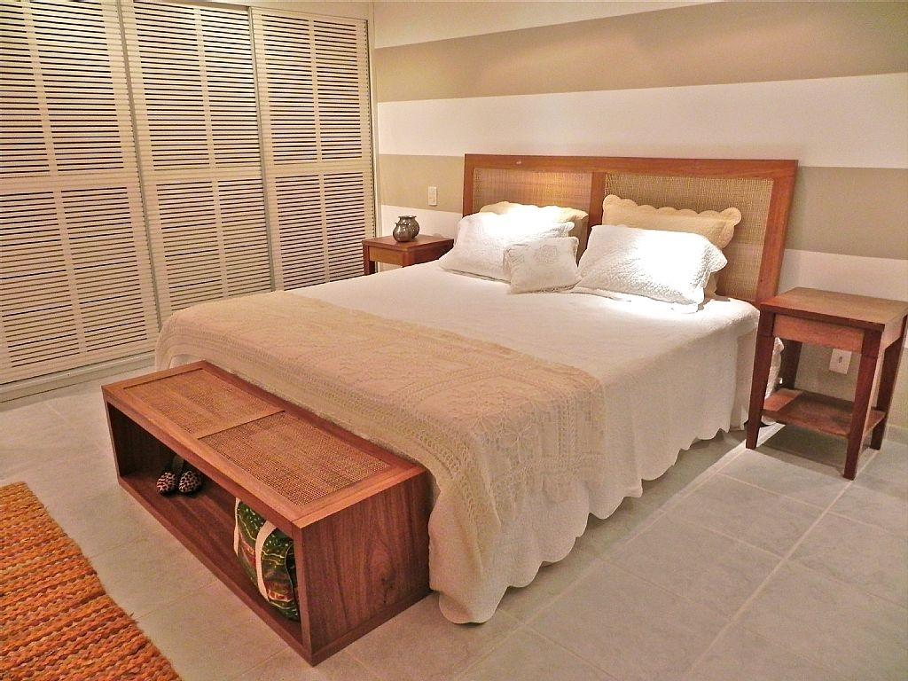 Quarto de casal com cabeceira da cama em palhinha, piso em ceramica e armarios com frestas que permitem a ventilação.