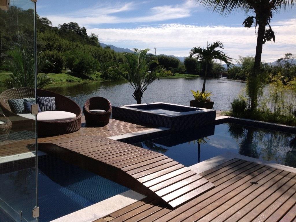 Deck em madeira com piscina e jacuzzi voltada para a vista do lago