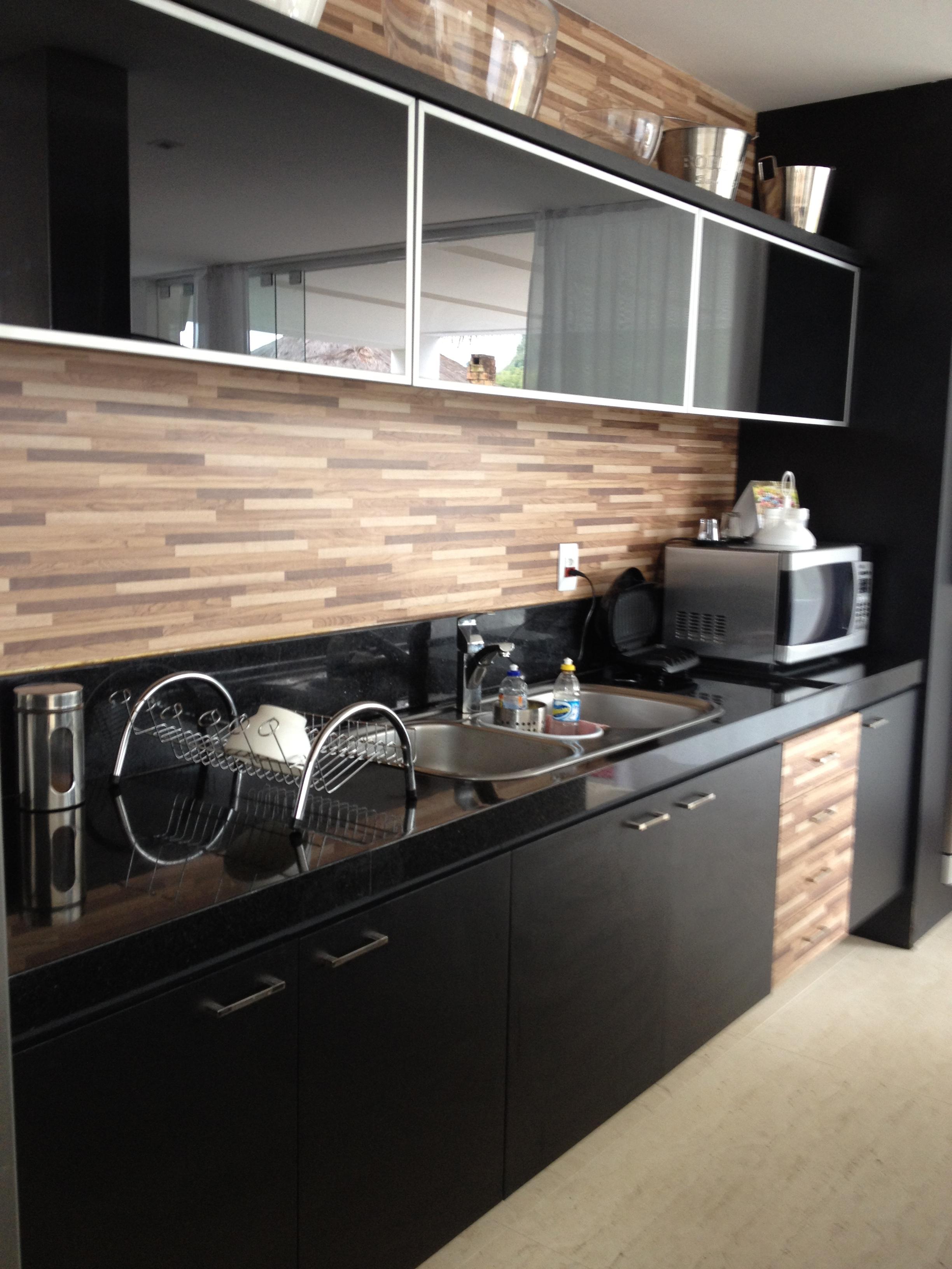 Cozinha com armarios em preto e revestimento em madeira ripada. #856646 2448x3264 Bancada Banheiro Leroy Merlin