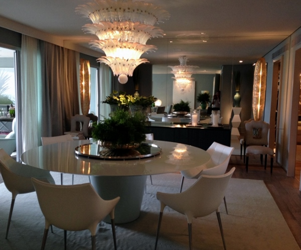 A sala de jantar mais escura é refletida por um grande espelho que emoldura um estenso aparador preto com duas cadeiras anos 50 em rosa claro. O lustre, também remete a 1950, em casacatas. Móveis brancos e contemporaneos completam o ambiente.