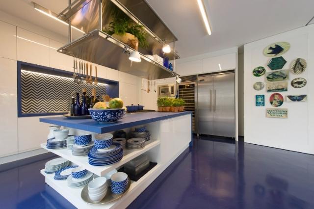 O piso em azul klein chega até a cozinha, onde o branco prevalece nas paredes. A ilha com bancada em corian azul deixa os utensílios a mostra, mais fáceis de encontrar em uma casa de praia.