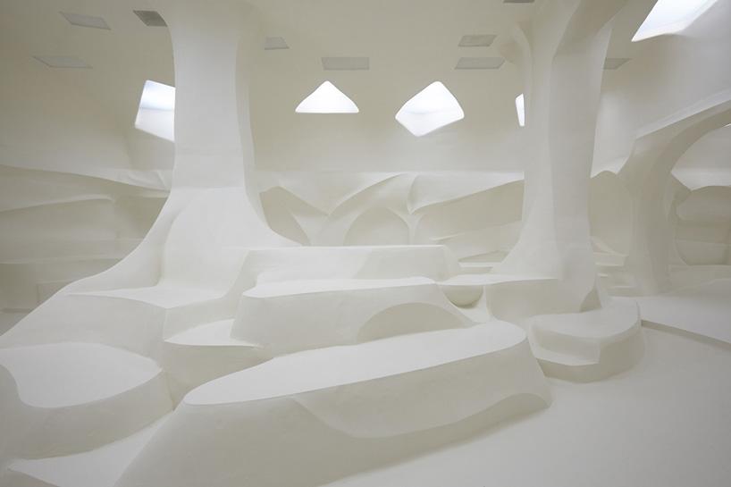 Como um casulo, o interior é uma grande escultura, cada curva foi sutilmente esculpida a mão por artesãos que esculpiram cada coluna, assentos, paredes e passarela. Tudo formando um bloco unico e organico.