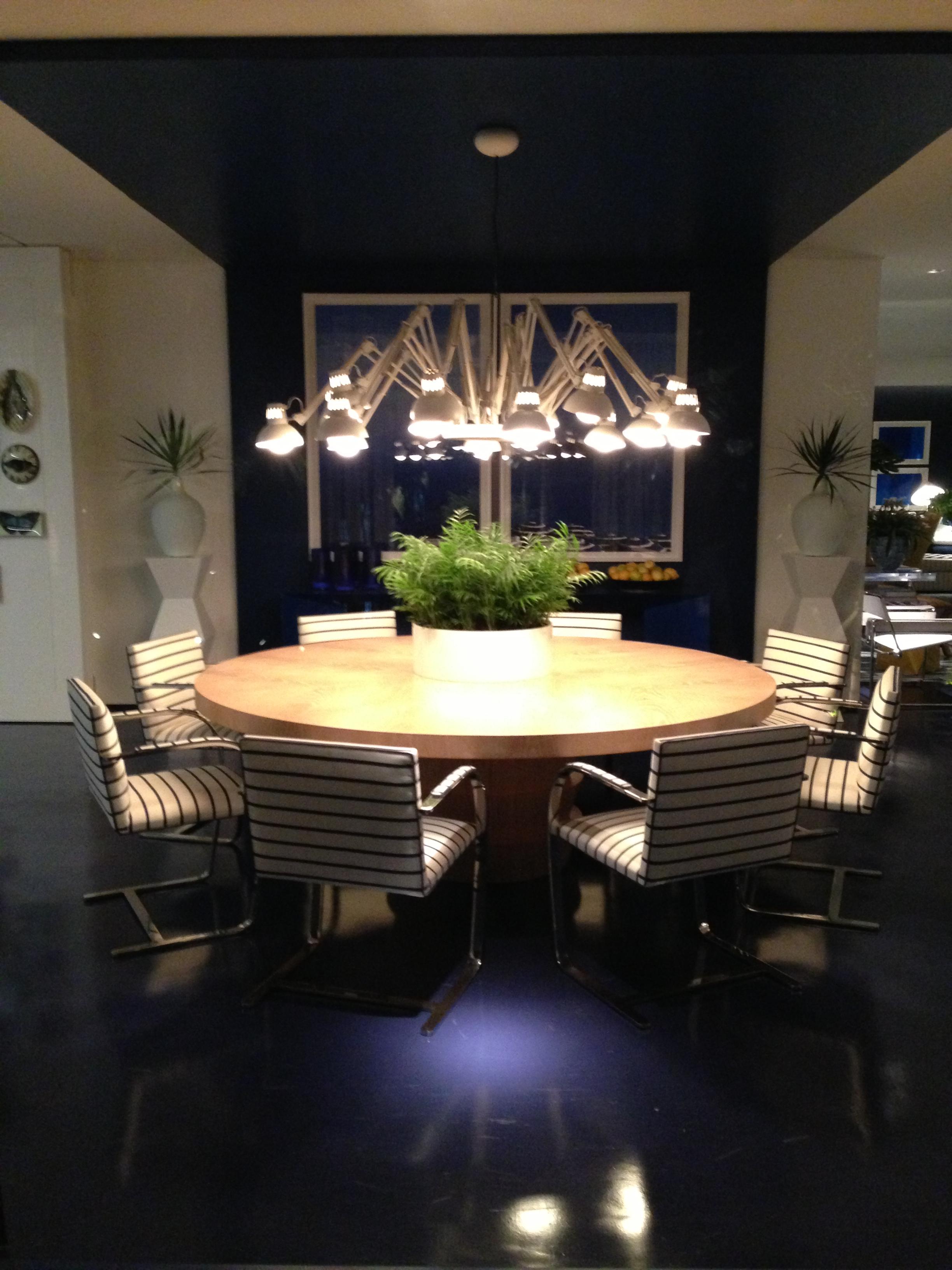"""Com o recurso de """"subir""""  o revestimento do piso à parede e teto delimita a sala de jantar. A mesa com cadeiras claras e o pendente com vários braços iluminam o ambiente."""