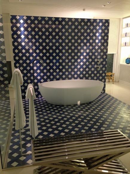 A sala de banho é um grande chamativo neste projeto, onde Migotto reproduziu o recurso usado na sala de jantar, mas com ladrilhos geométricos, criando um fundo para a banheira. O fechamento em vidro deu leveza ao ambiente, com todo o seu entorno, tanto piso como paredes e bancadas/armários em branco.