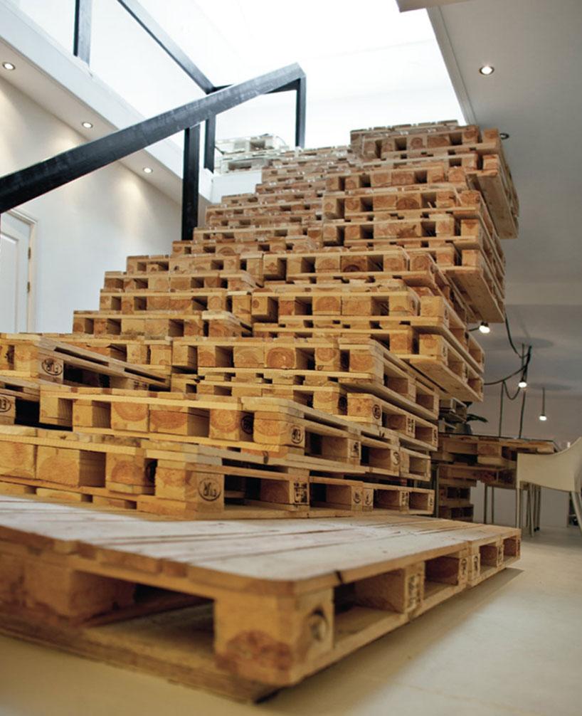 """Toda a escada foi feita pelo empilhamento dos pallets, deixando as alturas idênticas entre os degraus, embora, já no segundo piso, tenha sido necessário subir mais a escada para """"vencer"""" o pé direito do térreo. O corrimão em madeira pintada de preto se destacou no ambiente."""