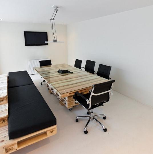 A sala de reunião ficou chic e descontraída com o extenso banco em pallets, com estofados em preto. Para completar cadeiras em inox e couro preto dão maior sofisticação ao ambiente sustentável. A luminária de braço é útil e contemporânea.