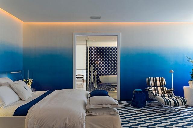 """Esse quarto fez muito sucesso, pelo uso do papel de parede degradê da Designer´s Guild criou um efeito """"fundo do mar"""", acentuado pela iluminação no topo das paredes. O ladrilho que reveste o piso e segue para a sala de banho proporciona um efeito vintage ao ambiente, harmonizando com os móveis modernistas e a cama sem cabeceira."""