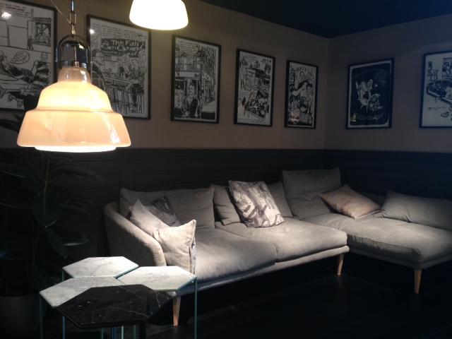 Ambiente do iSaloni 2014 com seqüência de quadros em preto e branco sobre parede bicolor, luminárias Foscarini e sofá ultra confortável da Moroso.