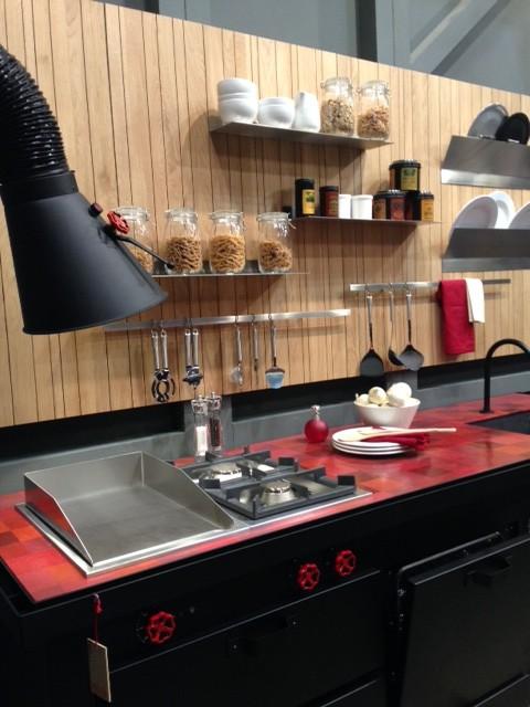 Coifa em estilo industrial, pintada de preto. Gostei dos suportes para pratos e tampas de panelas presos a parede.