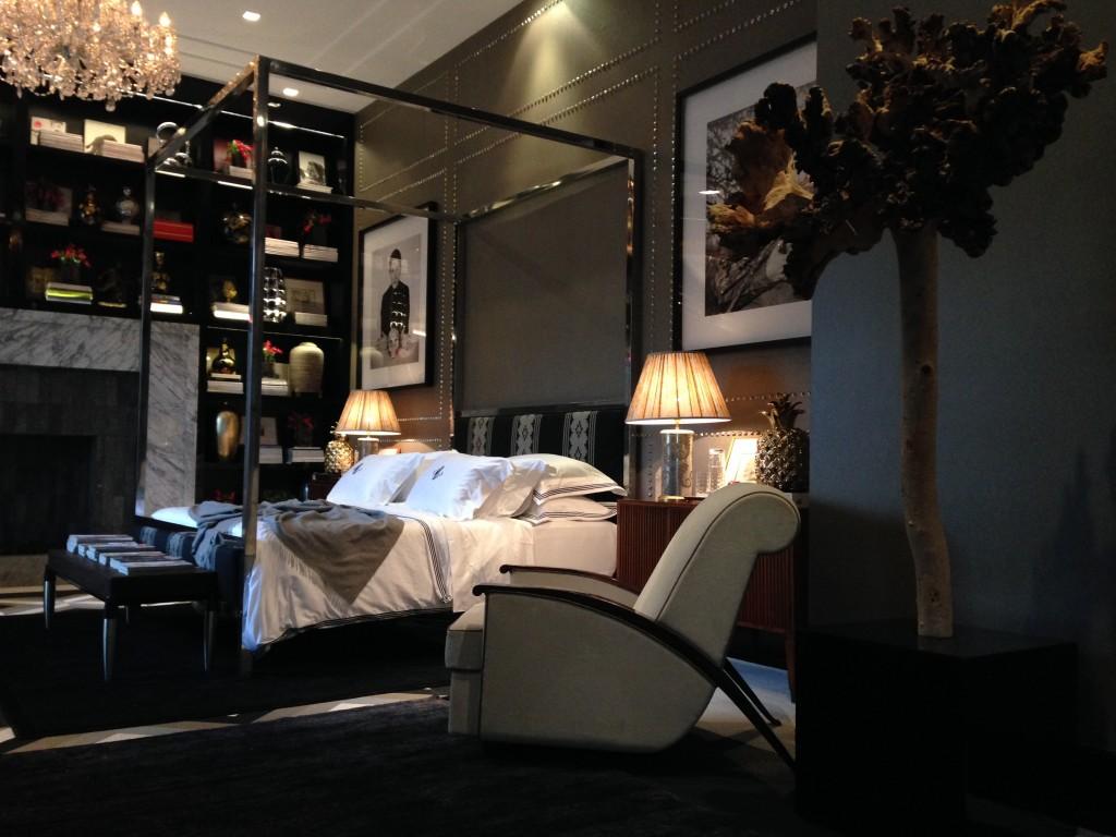 A cama, em medidas grandes também é limitada e demarcada por uma estrutura em inox. Auto retratos nas paredes e quadros também em grandes proporçoes são emoldurados por spikes a la Valentino sobre o papel de parede cinza.