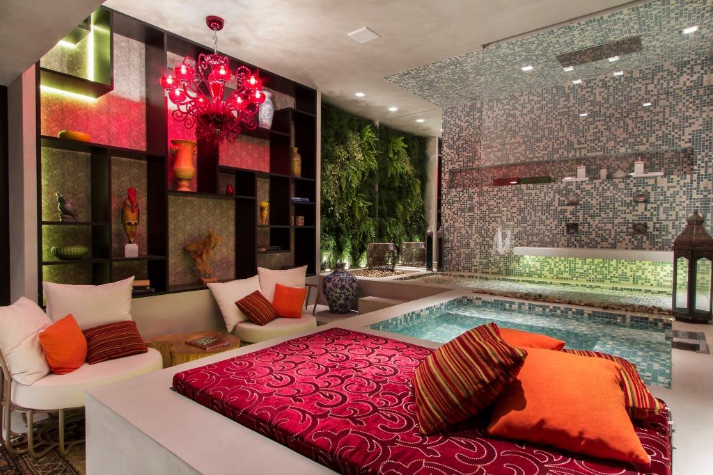 Relaxar em uma Sala de Banho, com champagne, luz baixa, almofadas, e alguns itens em vermelho para deixar o ambiente bem romântico foi uma solução que os arquitetos estreantes Claudia Alionis e Eduardo Bessa deram para a Sala de Banho no Casa Cor de São Paulo 2014.