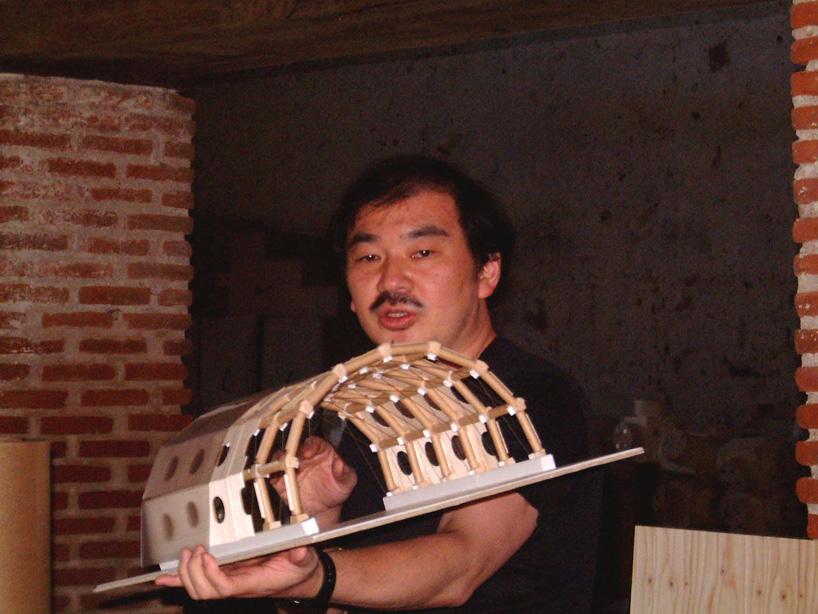 Shigeru Ban na época do projeto, com a maquete da estrutura em papelão.