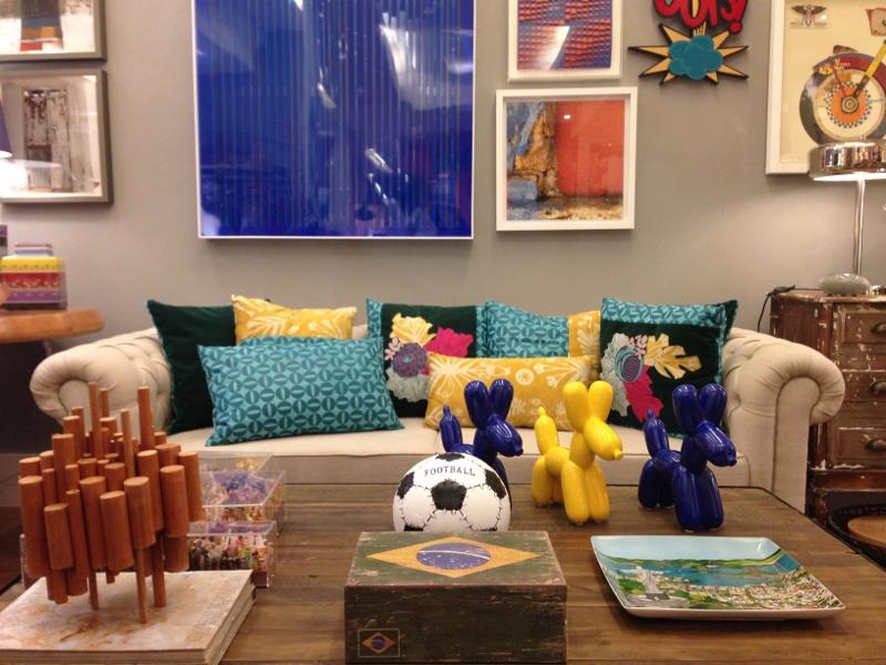 Já o Studio Grabowsky, no Leblon, está completamente no clima do Mundial!!! Caixa com a bandeira do Brasil, cachorrinhos (são cofrinhos fofos, inspirados em balões de gás em festas infantis, nas cores azul e amarelo, a bola retro (também um cofre), prato quadrado com imagem do Rio de Janeiro, além das almofadas no sofá são itens rápidos e fáceis de encaixar na decoração. Adorei!