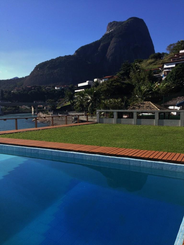 Área externa com a pedra da Gávea ao fundo e a piscina em primeiro plano.