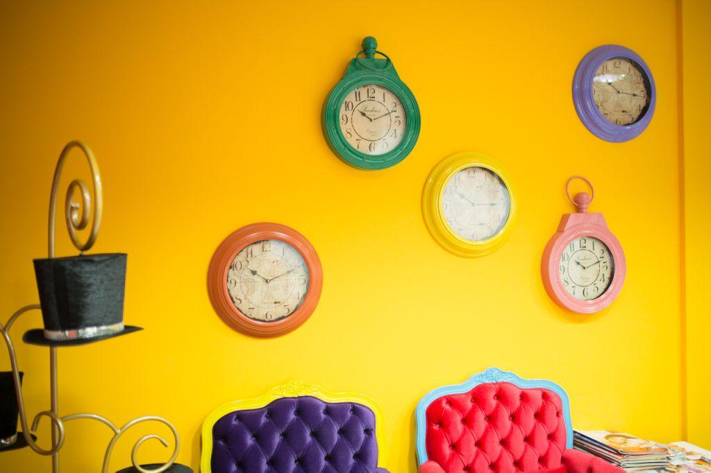 As poltronas de espera são todas coloridas. Na parede amarela, cinco relógios pautam a dúvida de Alice, de quanto tempo dura o eterno. No cabideiro, o trabalho do chapeleiro maluco é visto em três cartolas.