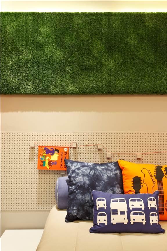 Painel em compensado, revestido com cortiça e com grama artificial por cima para fotos, recados, etc. Perto da cama, pequenos varais para pendurar obras de arte recém feitas pelas crianças.