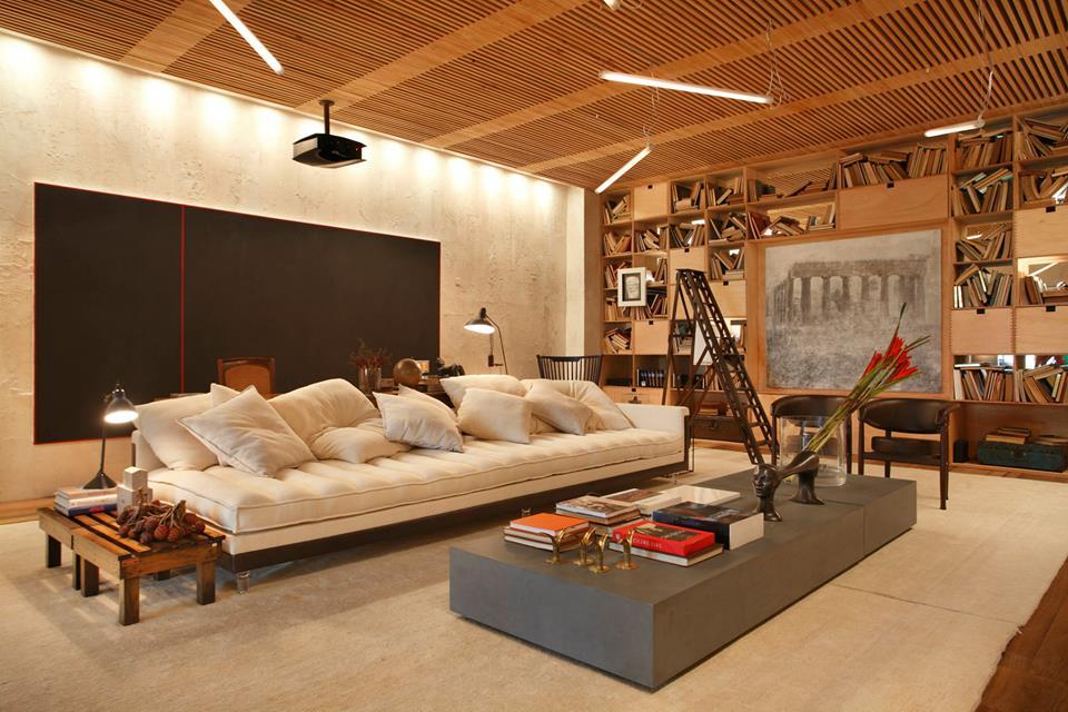 Grandes proporções: sofá de 4 metros, tela, mesa e o teto em madeira.