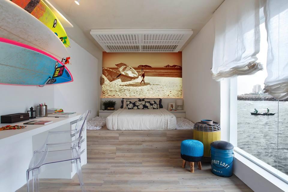 No teto, a arquiteta usou as divisórias de persianas para marcar a área da cama, com leves pendentes com pontos de LED que variam a coloração. A cabeceira, seguindo a nova tendencia de decoração, é uma foto com filtro envelhecido. Predominantemente branco, o ambiente ganhou vida com as pranchas de surf e pufes coloridos.